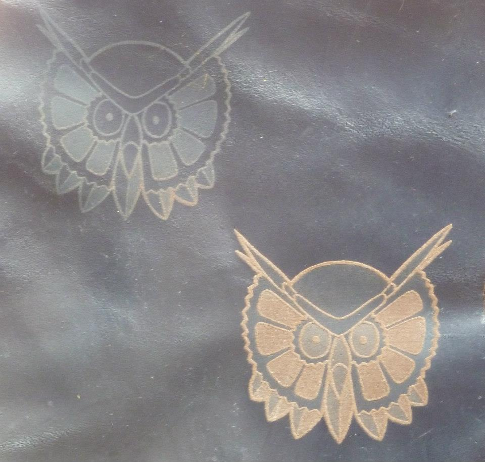 Engraved owl heads on leather
